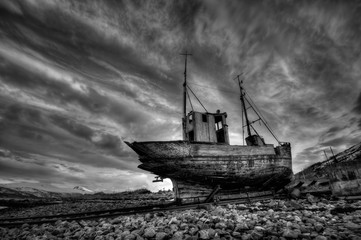Abandoned Ship At Beach Against Cloudy Sky