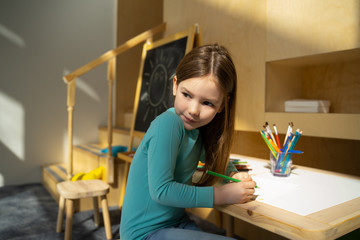 Adorable kid drawing in children playroom at home