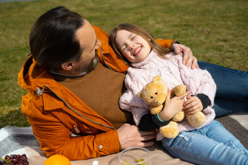 Cheerful little girl spending time with daddy outdoors