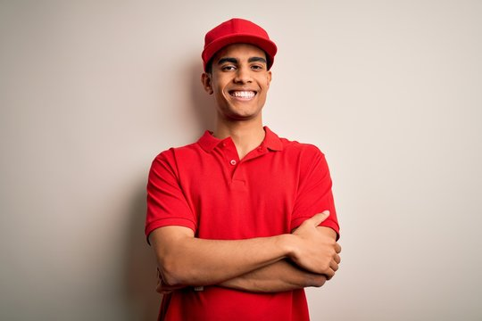 Young handsome african american man wearing casual polo and cap over red background happy face smiling with crossed arms looking at the camera. Positive person.