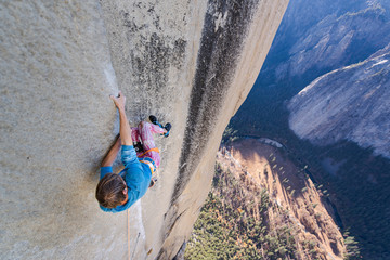 Climbing holding on sideway in crazy position to free climb the Nose