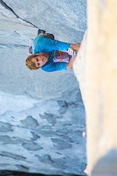 Rock climber looking up while climbing in Yosemite, El Capitan