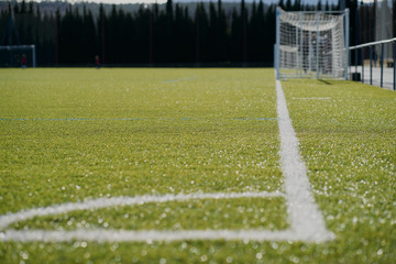 the white line in the football corner on the green field with the goal