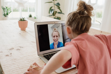 nurse having a video call with her family whilst working in a hospital