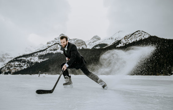 hockey player in suit stops fast kicking up frozen spray on lake