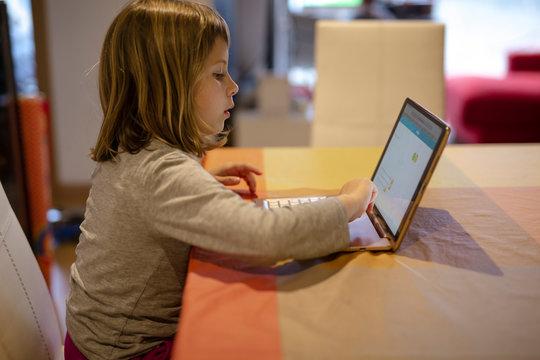 Blonde girl doing her homework on the tablet. Quarantine Covid-19