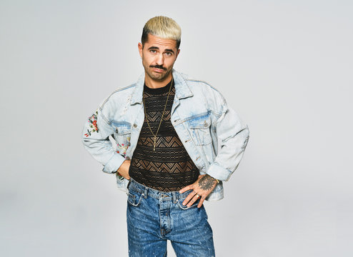 Young ethnic man making grimace doubting face looking at camera wearing trendy denim jacket with floral pattern while standing against gray background