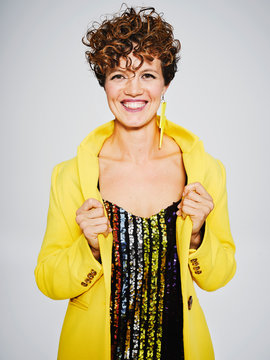 Cheerful woman with sequin top and lightning earring smiling and adjusting stylish yellow coat against gray background