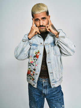 Young ethnic man making grimace doubting face with finger looking at camera wearing trendy denim jacket with floral pattern while standing against gray background