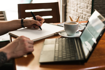 Unrecognizable man sketching in notepad near cup of coffee and laptop while sitting at table an working on remote project in cafeteria