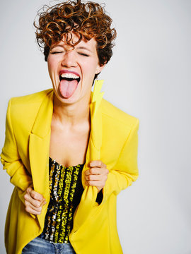 Funny adult female in stylish outfit closing eyes and showing tongue to camera against gray background