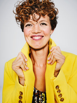 Portrait of cheerful woman with sequin top and lightning earring smiling and adjusting stylish yellow coat against gray background