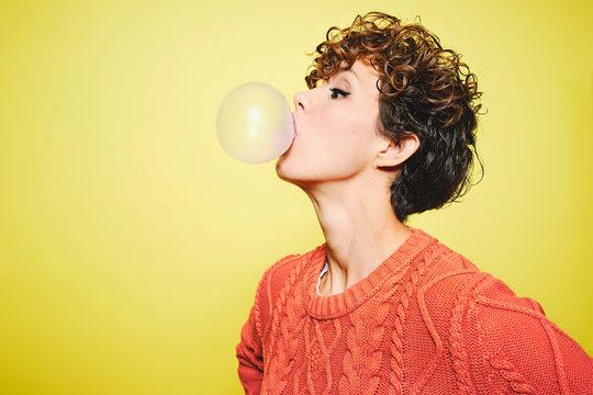 Side view of young pretty curly haired female in orange sweater blowing bubble gum while standing looking away against yellow background