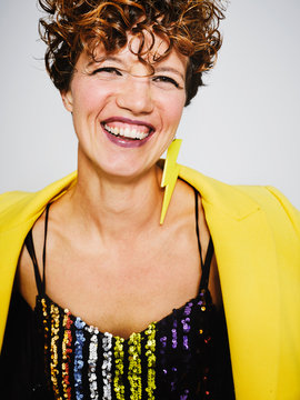 Portrait of cheerful woman with sequin top and lightning earring and stylish yellow coat smiling to the camera while standing against gray background