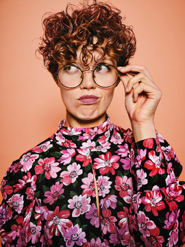 Thoughtful doubtful beautiful curly haired female in trendy eyeglasses and stylish colorful blouse with floral ornament looking away against pink background