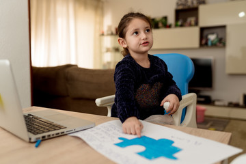 Little girl drawing creative banner while sitting at table with laptop in cozy room at home looking away
