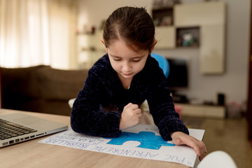 Focused little girl drawing creative banner while sitting at table with laptop in cozy room at home