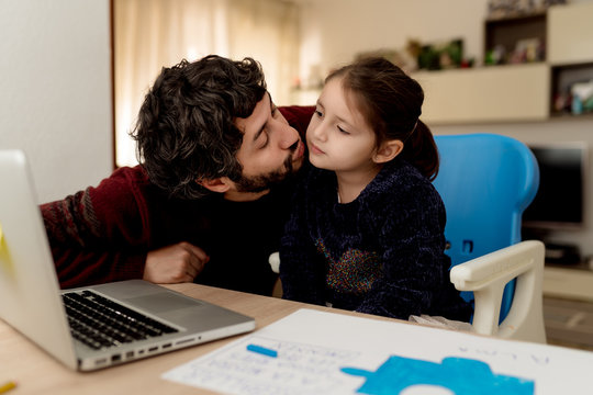 Bearded adult man sitting showing affection to a little girl with laptop and helping daughter with remote education while staying at home together