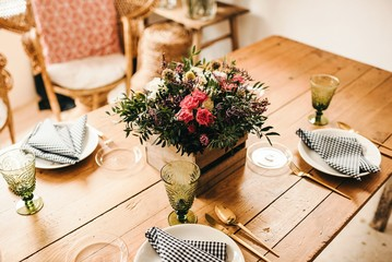 From above bouquet of miscellaneous flowers and green plant twigs in a wooden box on a timber table set for a meal with beautiful designed rattan chair on the background