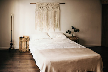 Vintage macrame decoration hanging on wall over comfortable bed in cozy bedroom at home