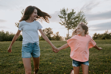 Cheerful carefree teen girl and youngest sister holding hands and running together on green meadow in summer day in countryside