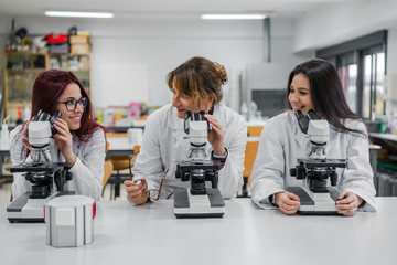 Female scientists using microscopes in lab
