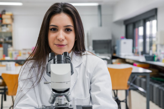 Young female scientist with microscope
