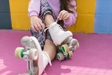 Crop young female in trendy outfit tying shoelaces on white quad roller skates while sitting on colorful playground in sunny day