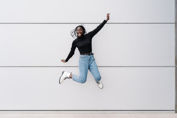 Full body delighted black female in casual clothes screaming and jumping against gray building wall on contemporary city street