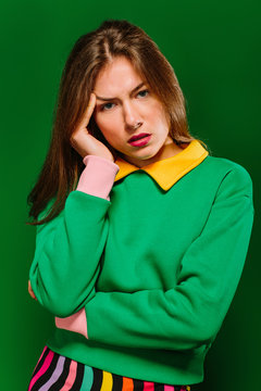 Young blonde woman model in stylish colorful outfit keeping hand near face and looking at camera thoughtfully while standing against green background