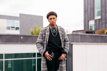 Serious young African American fashionable guy in trendy checkered coat and tight pants looking at camera while standing against modern buildings in city