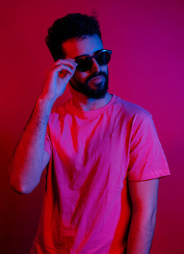 Confident bearded male in casual t shirt looking away and adjusting trendy sunglasses while standing under red light