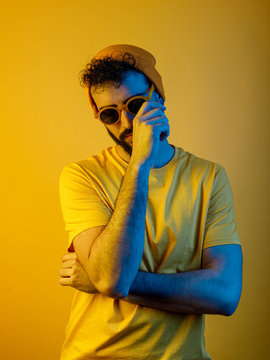 Serious bearded male in stylish sunglasses and hat touching face while standing under bright yellow light
