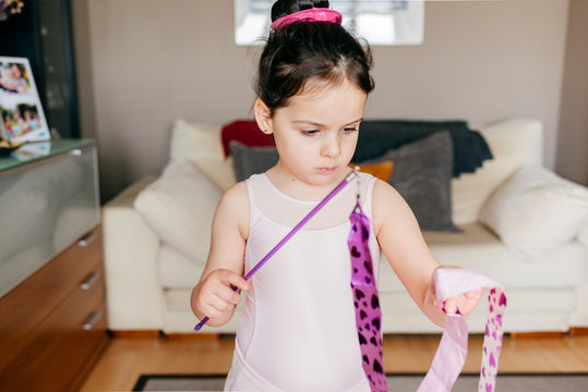 Focused cute little brunette girl in leotard looking away while spinning ribbon during rhythmic gymnastic practice training in cozy living room at home