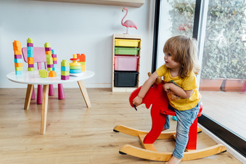 Side view of cute infant child in casual clothes having fun and riding red wooden horse while playing in kindergarten