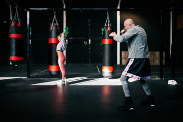 Side view of strong determined sportsman performing boxing exercise during workout in modern sport gym with training woman in background