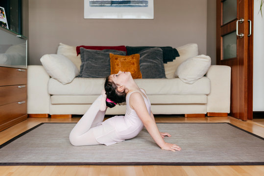 Side view of little girl in leotard looking up touching head with feet while doing gymnastic exercise on floor in cozy living room