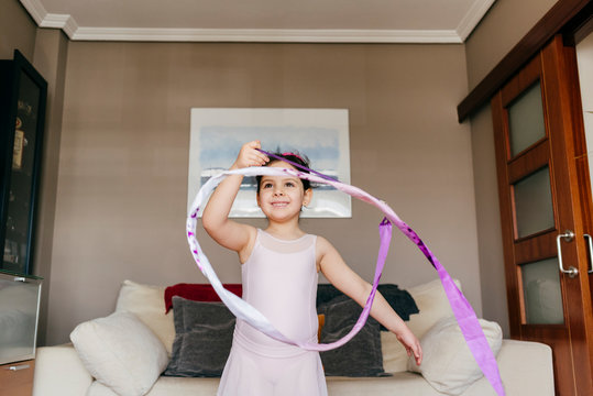 Focused happy cute little brunette girl in leotard looking away while spinning ribbon during rhythmic gymnastic practice training in cozy living room at home