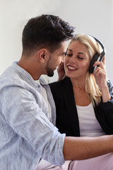 Cheerful woman in headphones smiling and trying to kiss ethnic boyfriend while listening to music at home together