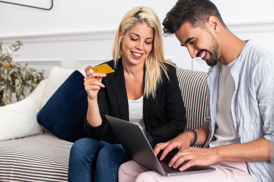 Delighted blonde female smiling and reading credit card credentials to cheerful ethnic boyfriend with laptop while sitting on sofa and making online purchases together
