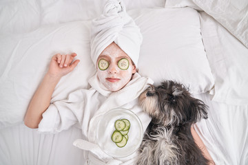 Top view of child in white bathrobe and towel turban with facial mask and cucumber slices on eyes lying on bed with fluffy dog while relaxing during spa procedure at home