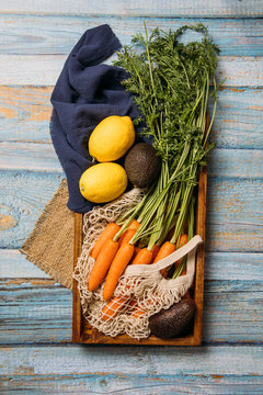 Top view of harvested ripe carrots with green foliage, lemon and fresh avocado placed on cutting board on wooden table with sustainable fish net shopping bag