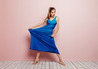 Young woman barefoot looking away stretching side of a blue dress while standing on minimalist pink background