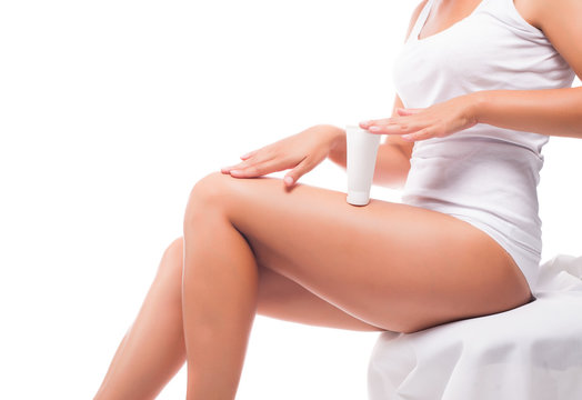 A woman puts body cream on her legs sitting on the bed, studio shooting.