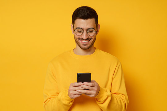 Young man looking at mobile phone screen through glasses, laughing at jokes sent by friends, dressed in bright clothes, isolated on yellow background