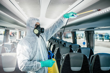 Professional chemical cleaning of bus seats. Bus disinfection. Exterminator in workwear.