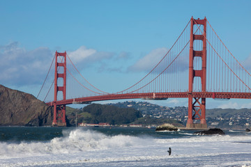 A lone fisherman fishes in the waves next to the famous Golden Gate Bridge in San Francisco.