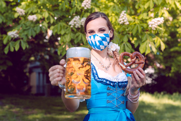 Bavarian woman toasting with beer during covid-19