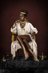 A gorgeous young female Egyptian Pharaoh wearing elegant clothing, a gold crown and jewelry is sitting on her golden throne.