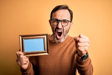 Middle age hoary man wearing glasses holding vintage frame over isolated yellow background annoyed and frustrated shouting with anger, crazy and yelling with raised hand, anger concept